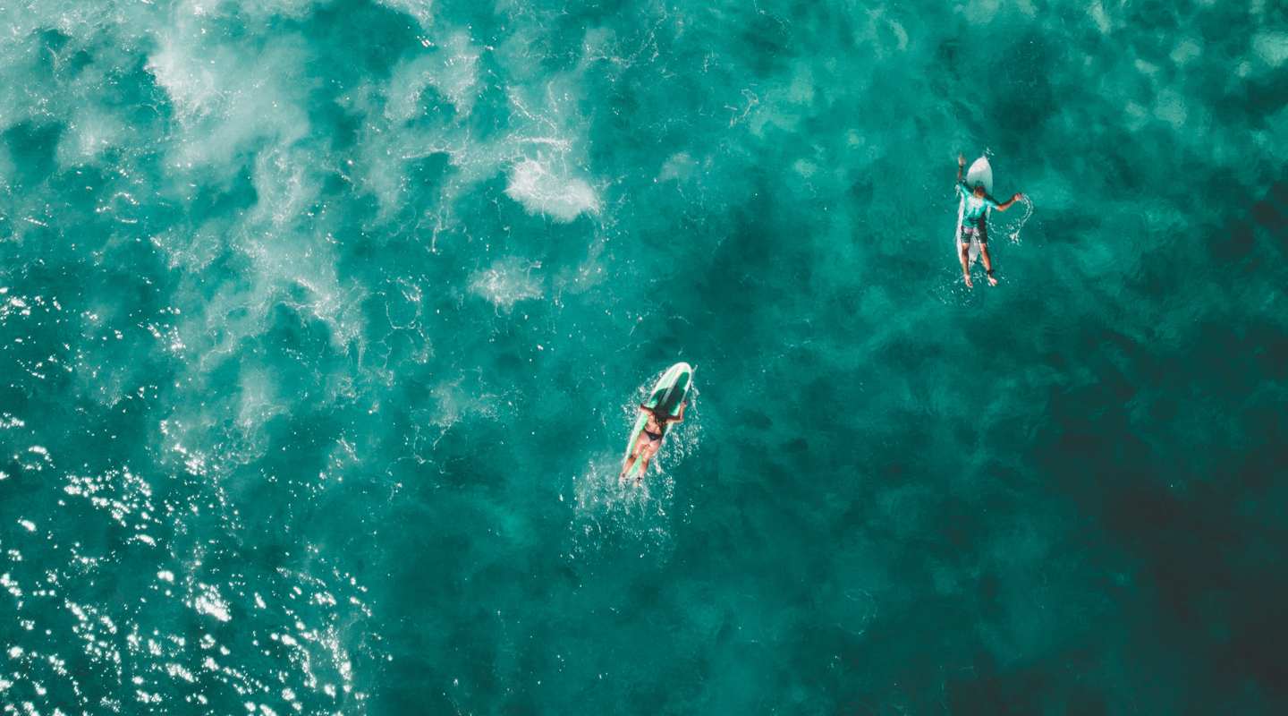 Aerial view of surfers in turquoise water