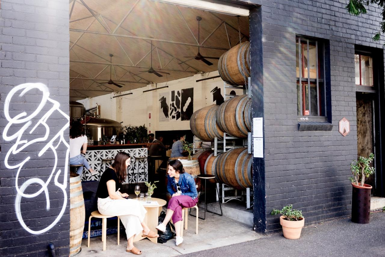 Large wooden barrels sit just inside this warehouse brewery while two women talk and drink beer